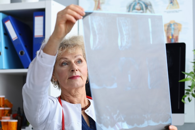 De arts met rode stethoscoop onderzoekt röntgenstraal in afdeling
