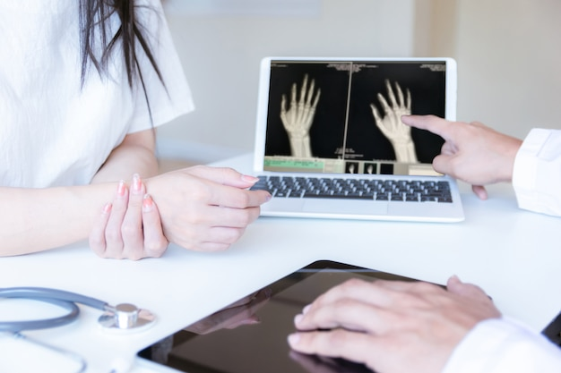 De arts onderzocht de patiënt met polspijn en een röntgenfoto