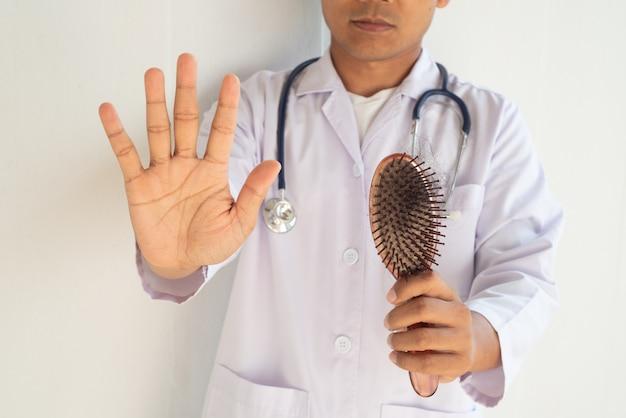De arts onderzoekt de haarborstel om haarverlies te bewijzen