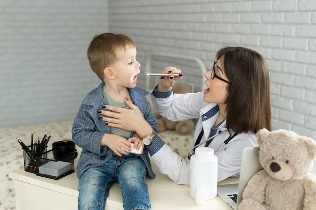 De arts onderzoekt de keel van het kind. jongen bij kinderarts kantoor.
