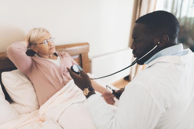 De arts onderzoekt een oudere patiënt in een verpleeghuis