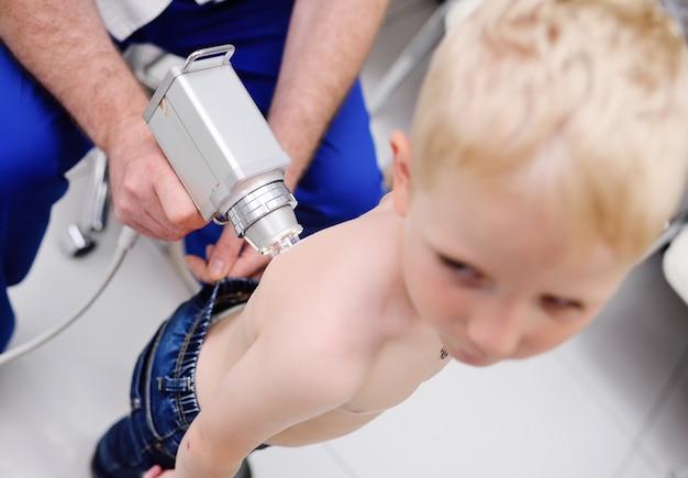 De arts onderzoekt het speciale medische apparaat mollen kind