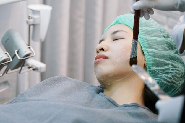 De arts past hydro-gelmasker op het vrouwengezicht toe. voordat jonge vrouw laserbehandeling krijgt.