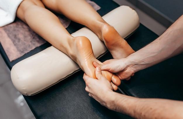 De arts-podoloog doet in de kliniek onderzoek en massage van de voet van de patiënt.