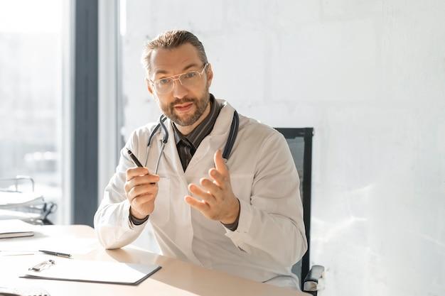De arts praat met de patiënt en legt de patiënt de bijzonderheden van diagnose en behandeling uit.