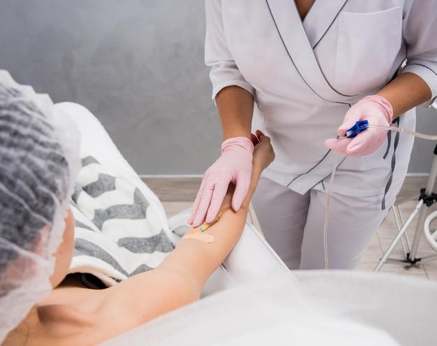 De arts-schoonheidsspecialist maakt de procedure voor het druppelen van cosmetica. infusie. jonge vrouw in een schoonheidssalon.