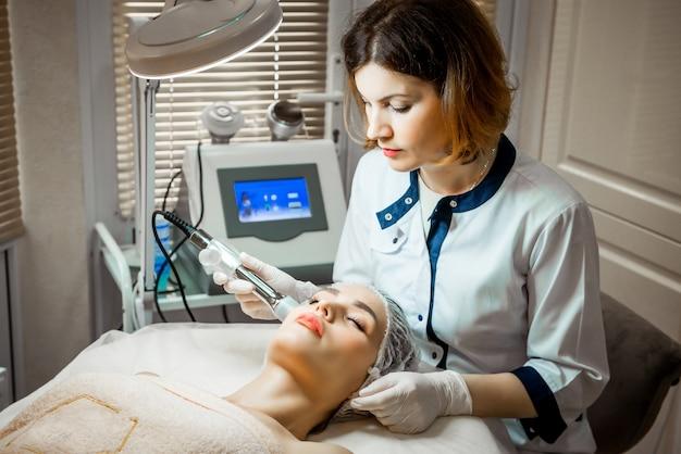 De arts-schoonheidsspecialist maakt de verjongende gezichtsinjectieprocedure voor het aanhalen en gladmaken van rimpels op de gezichtshuid van een mooie, jonge vrouw in een schoonheidssalon