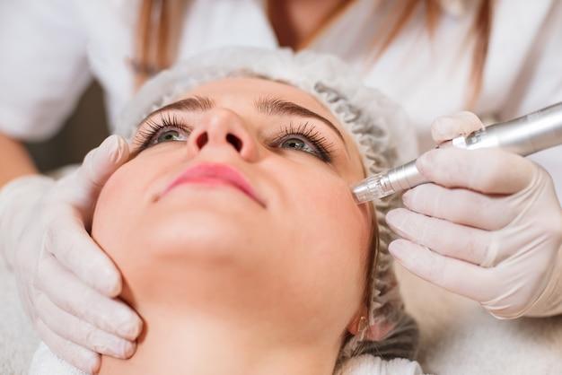 De arts-schoonheidsspecialist maakt een procedure voor het ultrasoon reinigen van de gezichtshuid