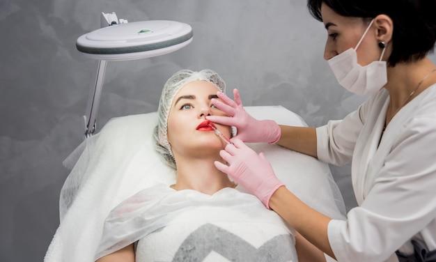De arts-schoonheidsspecialist voert de procedure voor gezichtsinjecties uit. jonge vrouw in een schoonheidssalon.