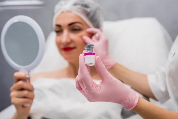 De arts-schoonheidsspecialist voert de procedure voor gezichtsinjecties uit.