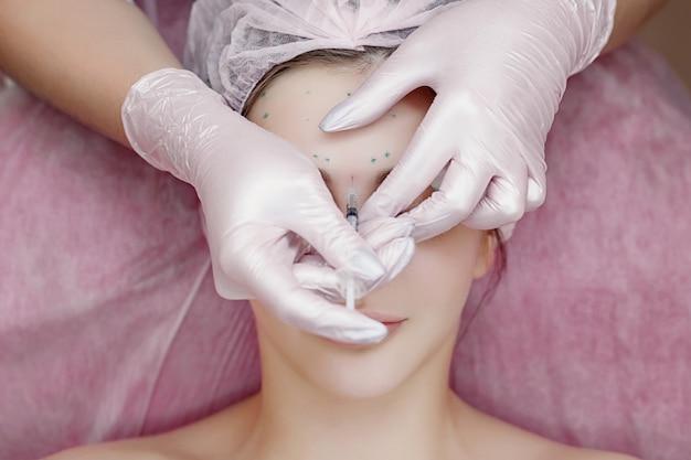 De arts-schoonheidsspecialist voert de procedure voor verjongende gezichtsinjecties uit om rimpels op de huid van het gezicht van een mooie, jonge vrouw in een schoonheidssalon aan te halen en glad te strijken.