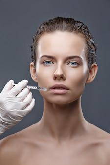 De arts-schoonheidsspecialist voert de procedure voor verjongende gezichtsinjecties uit