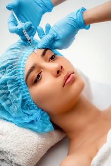 De arts-schoonheidsspecialist voert de verjongingsbehandeling voor gezichtsinjecties uit om rimpels op de gezichtshuid van een vrouw in een schoonheidssalon aan te halen en glad te maken. cosmetologie huidverzorging