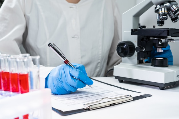 De arts schrijft de resultaten van een bloedtest op een formulier. werkplaats van de arts - microscoop, reageerbuizen met bloed