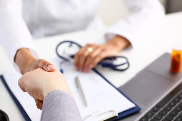 De arts schudt hand als hallo met patiënt