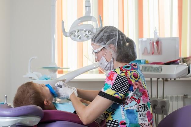 De arts-tandarts van jonge kinderen behandelt tanden met verschillende apparaten