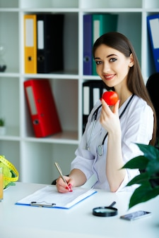 De arts tekent een dieetplan af. de diëtist houdt de handenvol verse tomaat in de hand. fruit en groenten.