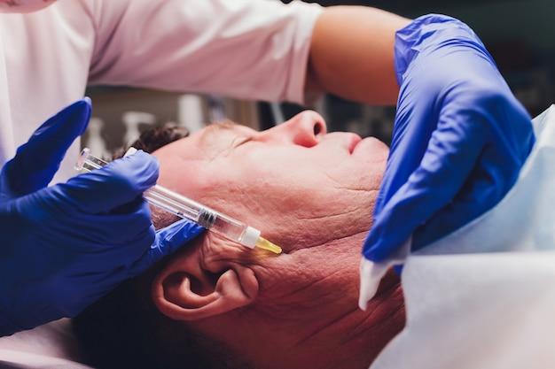 De arts trekt een punt voor injecties op het gezicht van de patiënt. voorbereiding voor biorevitalisatie close up.