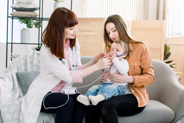 De arts van de vrouw houdt een inhalator van de maskerdamp voor weinig babymeisje. behandeling van astma. ademen door een stoomvernevelaar. concept inhalatietherapieapparaat.