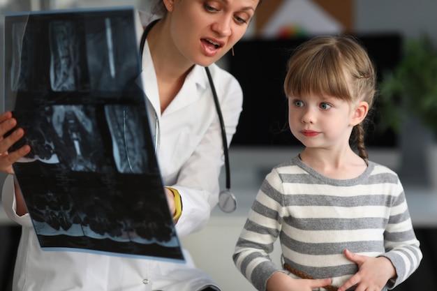 De arts van het kind kijkt x-ray beeld in het ziekenhuis