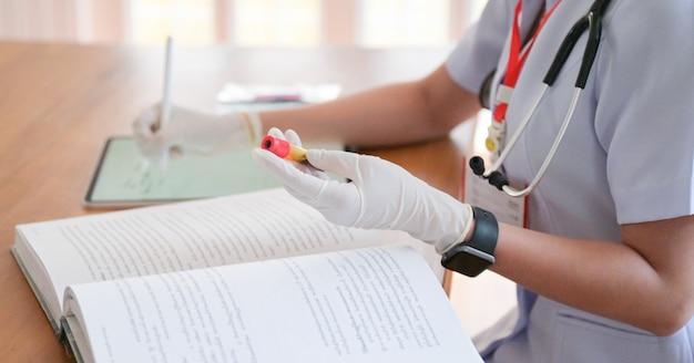 De arts zoekt behandelingsinformatie om de resultaten van een bloedonderzoekbuisje met een tablet te vergelijken