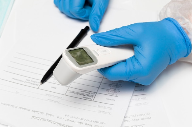 De artsen handen in handschoenen houden een contactloze thermometer vast om de temperatuur te meten voordat ze worden gevaccineerd bij covid19 het concept van medische gezondheidsvaccinatie tegen covid19-virus