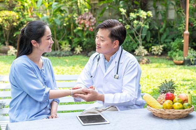 De artsen werkende baan neemt zorg aan vrouwenpatiënt bij openluchtpark, hulpverzekeringsgezondheid neemt zorgconcept