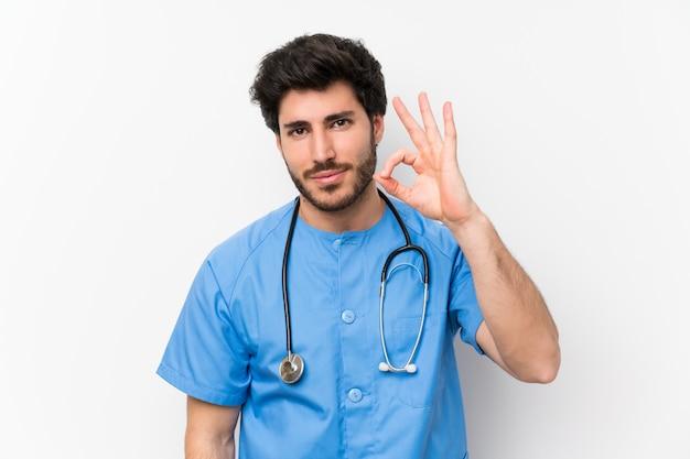 De artsenmens van de chirurg over geïsoleerde witte muur die een ok teken met vingers toont