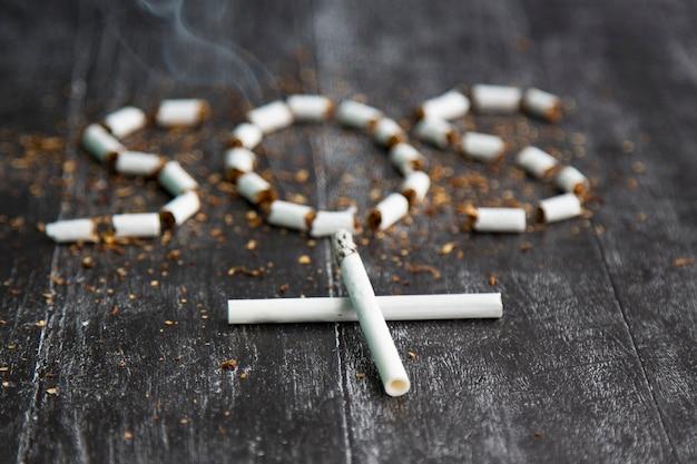 De as en de sigaret zien eruit als een kruis, een artistiek concept voor werelddag zonder tabak. teken sos van tabak. gezondheidsrisico's van nicotine. de sigaret is dodelijk. zwart-wit donkere foto