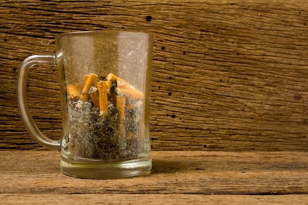 De asbaksigaret van het glasbier op oud hout