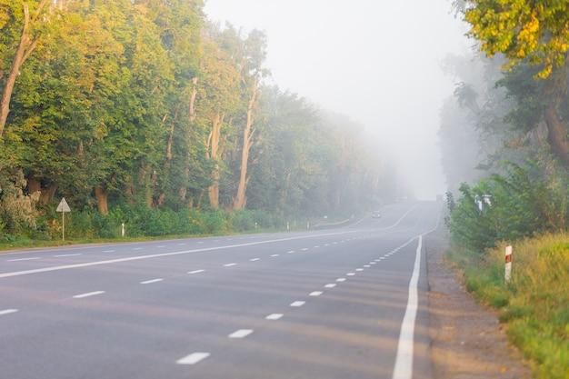 De asfaltweg buiten de stad en dikke mist erboven in de ochtend
