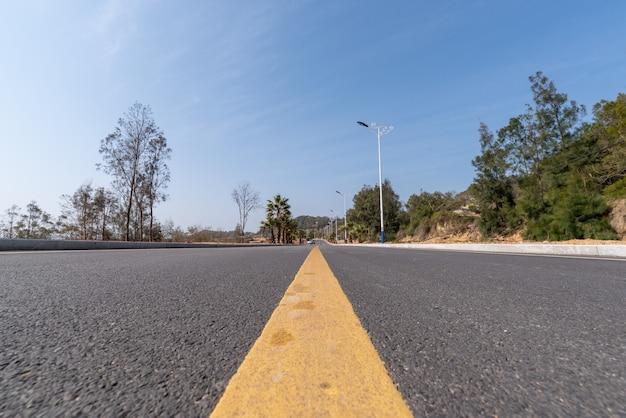 De asfaltweg die naar de verte leidt, is onder de blauwe lucht