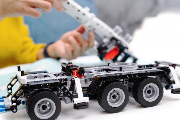 De assemblagekit van de auto, vrouw assembleert een zeer ingewikkeld en gemeenschappelijk stuk speelgoed van de autovrachtwagen.