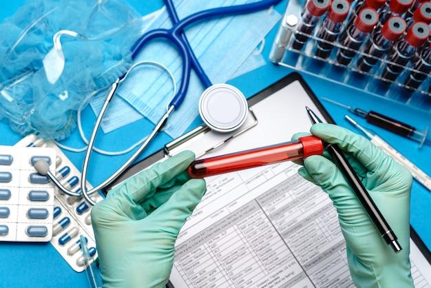 De assistent of de arts van de laboratoriumtechnicus die rubber of latexhandschoenen dragen die bloedonderzoekbuis over klembord met leeg formulier houden.