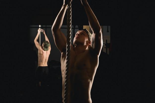 De atleet die geschiktheidskabel doen beklimt oefening in de training van de geschiktheidsgymnastiek