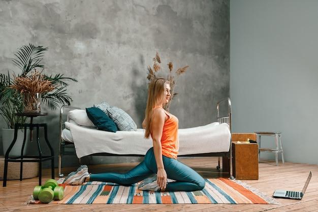 De atleet strekt zich uit, mediteert, zittend op een vloer in de slaapkamer