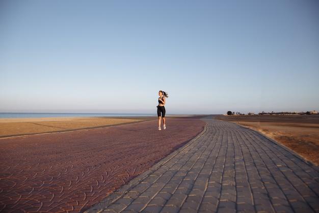 De atleet van het meisje in een zwart trainingspak en sneakers loopt door de zee tijdens zonsondergang