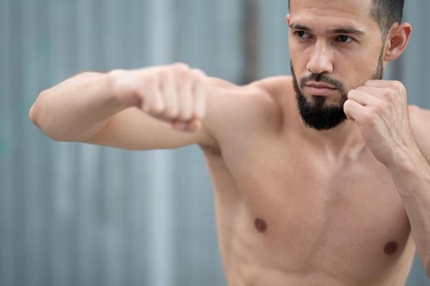 De atleet vecht met de schaduw. een bokser traint stoten op straat