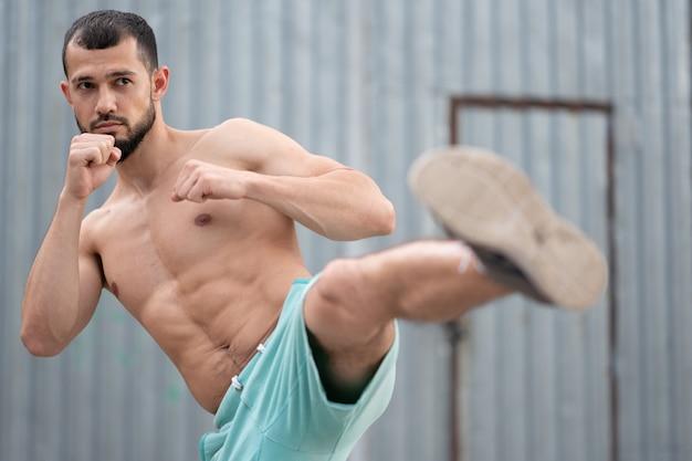 De atleet vecht met een schaduw. kickboxer traint trappen op straat