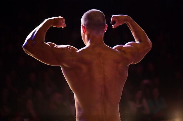 De atleetbodybuilder van prestaties aan concurrentie. demonstratie van biceps je armen van achter close-up