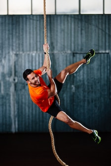De atletenmens die van crossfit een kabel in gymnastiek beklimt