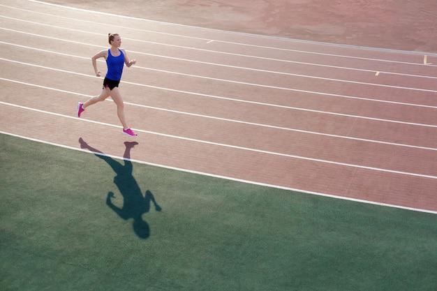 De atletische jonge vrouw in roze tennisschoenen loopt op renbaanstadion