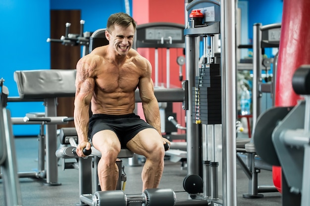 De atletische sterke bodybuilder voert oefening in sportzaal uit op de ongelijke bars