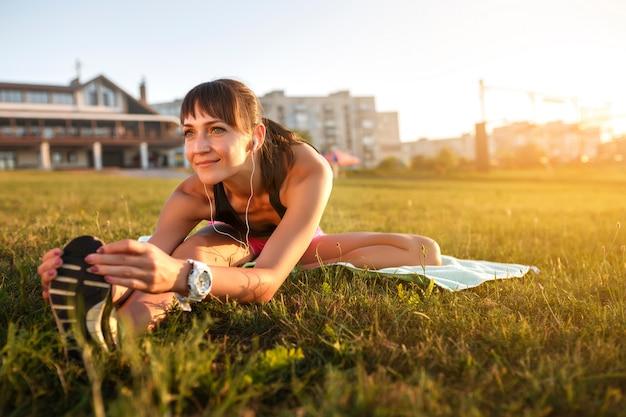 De atletische vrouw die haar uitrekken verlamt, benen oefent opleidingsgeschiktheid uit vóór training buiten met hoofdtelefoons het luisteren muziek.
