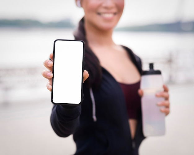 De atletische vrouw die van de close-up mobiele telefoon houdt