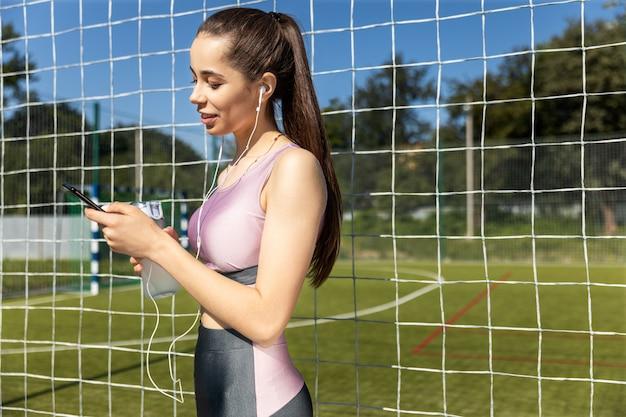 De atletische vrouw in de sportieve uitrusting luistert muziek