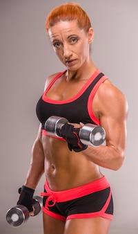De atletische vrouw pompt spieren met domoren op.