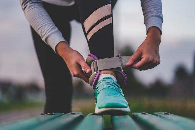De atletische vrouw zet sportgewichten op om tijdens training openlucht te lopen. gezonde en sportieve levensstijl.