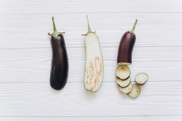 De aubergine wordt verscheurd op de witte houten achtergrond, hoogste mening.