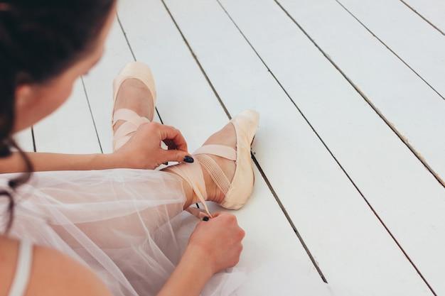 De authentieke ballerina balletdanseres zittend op de vloer en koppelende pointe schoenen